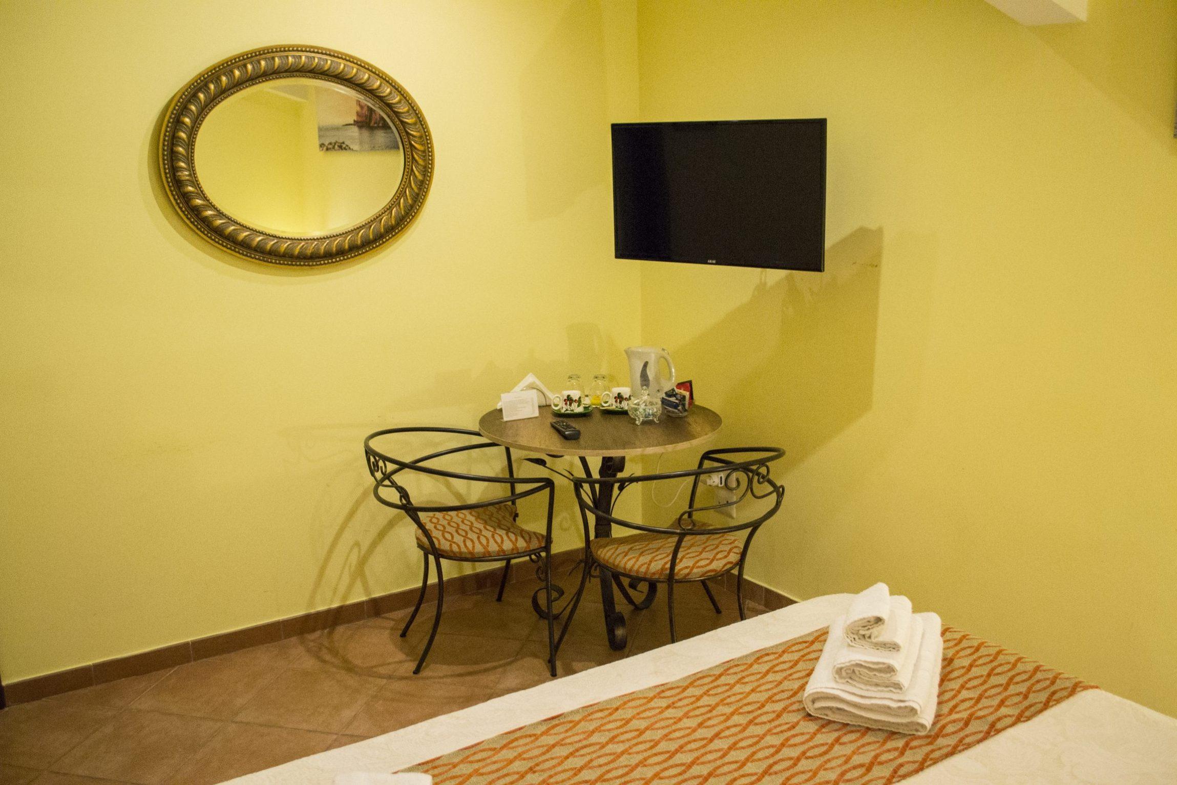 camera, marimoniale, la gemma, napoli, tavolo, sedie, tv led, specchio, dettagli
